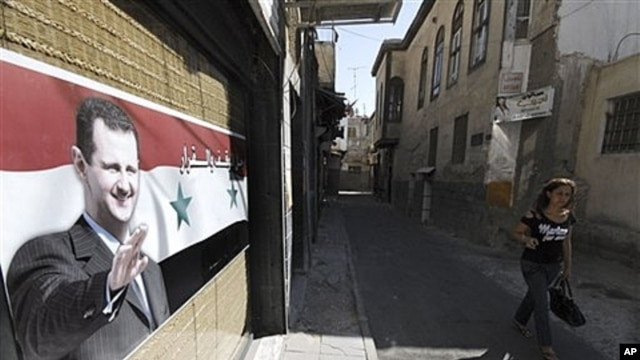 A woman passes a poster in support of President Assad, Damascus, September 15, 2011.