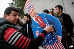 Plainclothes police officers take away an effigy of President Barack Obama as members of the Turkey Youth Union gather to protest the upcoming visit of Obama to Turkey in mid-November for G20 summit in Antalya, outside the US consulate in Istanbul, Nov. 8, 2015.