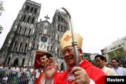 FILE - Catholic Archbishop of Hanoi Peter Nguyen Van Nhon waves to believers in front of St. Joseph Cathedral after Sunday mass in Hanoi, May 23, 2010.