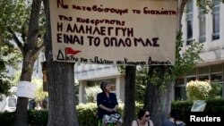 Supporters of the employees of state broadcaster ERT sit outside its headquarters in Athens, June 17, 2013.