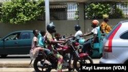 Un conducteur de moto remorquant 3 passagers à Lomé, le 14 août 2019. (VOA/Kayi Lawson)