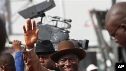 Nigeria President Goodluck Jonathan, center, wave to his supporters during the final campaign rally, at Eagle Square in Abuja, March 26, 2011