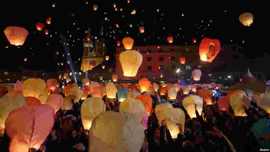 """Des participants tiennent des lanternes lors de la cérémonie """"Kapulica et Lanterns"""" au Zagreb. Les lanternes symbolisent les vœux de chaque personne pour Noël. Zagreb, 22 décembre 2014."""
