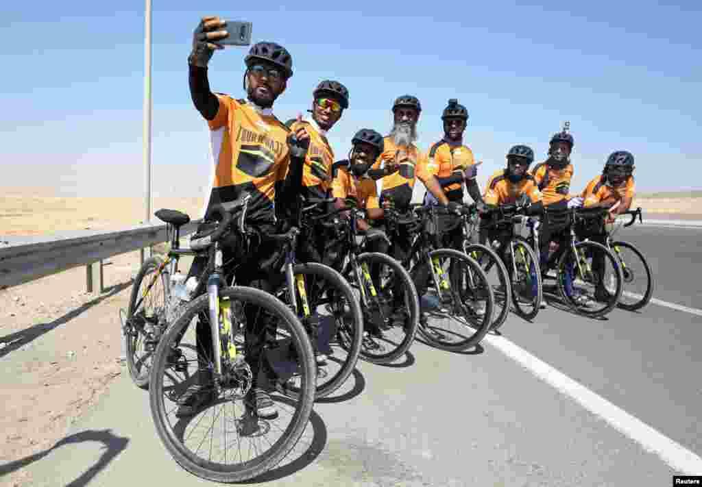Delapan Muslim dari Inggris yang bersepeda dari London ke Madinah untuk menunaikan ibadah Haji, berswafoto saat tiba di Kairo, Mesir, 26 Juli 2019. (Foto: Reuters)