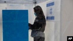 Seorang sukarelawan mengenakan masker, memperagakan bagaimana seorang yang dikarantina akibat terkena virus korona mengikuti pemilihan dalam tenda khusus di sebuah TPS di Tel Aviv, Israel, 1 Maret 2020. (Foto: dok).