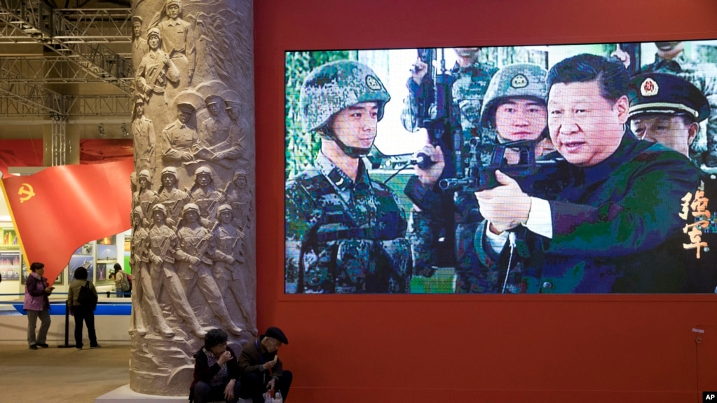 A video showing Chinese President Xi Jinping handling an assault rifle is shown at an exhibition highlighting China's achievements under five years of his leadership at the Beijing Exhibition Hall in Beijing, , Oct. 19, 2017.