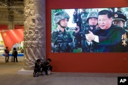 In this Oct. 19, 2017, photo, video showing Chinese President Xi Jinping handling an assault rifle is shown at an exhibition highlighting China's achievements under five years of his leadership.