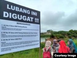 Aktivis lingkungan memasang plang sebagai bentuk protes atas lubang tambang yang belum direklamasi. (Sumber: Jatam Kaltim)