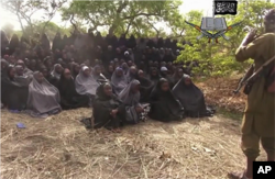 FILE - This file photo taken from video by Nigeria's Boko Haram terrorist network, May 12, 2014, shows the missing girls alleged to be abducted April 14, from the northeastern town of Chibok.