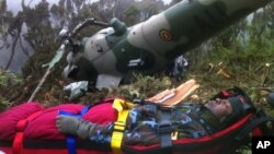 In this photo provided by the Kenyan military, Chris Kasiji, a senior Ugandan air force pilot, is rescued from the wreckage of a helicopter on Mount Kenya, August 13, 2012.
