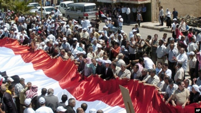 Syrian supporters of President Bashar Assad carry a giant national flag during a protest in al-Qarya village, in the southwestern Suwayda province, Syria, July 1, 2011