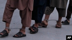 FILE - Recaptured Afghan prisoners walk in leg chains in jail in Kandahar, Afghanistan, April 26, 2011.
