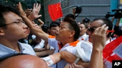 Pro-Beijing supporters (C and R) clash with pro-democracy protesters (L) during a rally to promote the Hong Kong electoral reform in Hong Kong, April 25, 2015.