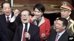 Le président chinois Jiang Zemin et le vice-Premier ministre Qian Qichen (à gauche), Yu Yongbo, le directeur du Département politique général de l'APL (arrière droite), chef de la direction de Macao Il Houhua (deuxième à droite) et d'autres chantent lors d'une cérémonie du retour de Macao à la Chine, le 20 décembre 2000.