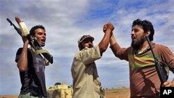 ພວກນັກລົບຂອງຝ່າຍປະຕິວັດລີເບຍພາກັນສະແດງຄວາມຍິນດີ ໃນລະຫວ່າງການບຸກໂຈມຕີເມືອງ Libya ບ້ານ ເກີດຂອງກາດດາຟີ (6 ຕຸລາ 2011)