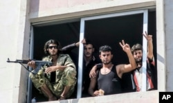 FILE - Free Syrian Army fighters gesture in Jarablus, Syria, Aug. 31, 2016.