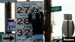 A man changes the price for a gallon of gasoline at a gas station in Medford, Massachusetts.