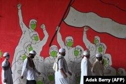 Pria Muslim berjalan melewati mural yang menampilkan orang-orang yang mengenakan masker selama pandemi COVID-19 di Jakarta pada 29 Januari 2021. (Foto: AFP/Adek Berry)