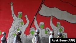 Rombongan Pria Muslim berjalan melewati mural yang menampilkan orang-orang yang mengenakan masker selama pandemi COVID-19 di Jakarta pada 29 Januari 2021. (Foto: AFP/Adek Berry)