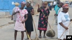 FILE - A group of women sweep a main street in the fishing village of Cotes-de-Fer, Haiti, Oct. 25, 2014.