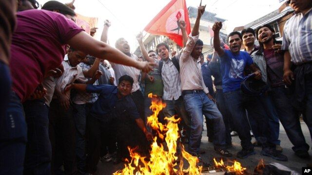Members of Nepal Student Union affiliated with Nepali Congress chant slogans while they burn an effigy of Prime Minister Baburam Bhattarai in Katmandu, Nepal, May 31, 2012.