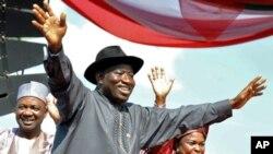 Shugaban kasar Najeriya Goodluck Jonathan (C),tare da matarshi Patience (R), Mataimakin shugaban kasa Namadi Sambo, yana dagawa jama'a hannu kafin kaddamar da kamfen dinsa a Abuja.