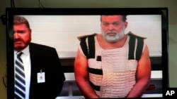 Colorado Springs shooting suspect Robert Lewis Dear, right, appears via video before Judge Gilbert Martinez, with public defender Dan King, at the El Paso County Criminal Justice Center for this first court appearance.