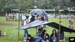 Refugees take cover from the rain under an improvised shelter at a military zone for people displaced by earthquakes in Cuilapa, Guatemala, September 19, 2011.