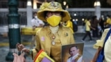 A royalist supporter holds a portrait of the late king Bhumibol Adulyadej while waiting for the motorcade of Thailand's King Maha Vajiralongkorn to pass in Bangkok.