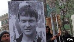 去年3月莫斯科的一次反政府集會要求釋放政治犯,一名示威者手舉拉茲沃茲扎耶夫的頭像。(美國之音白樺拍攝)