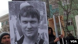 去年3月莫斯科的一次反政府集会要求释放政治犯,一名示威者手举拉兹沃兹扎耶夫的头像。(美国之音白桦拍摄)