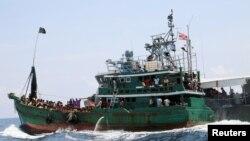 Un bateau avec des migrants est remorqué par un navire de la marine thaïlandaise, dans les eaux proches de l'île de Koh Lipe le 16 mai 2015.