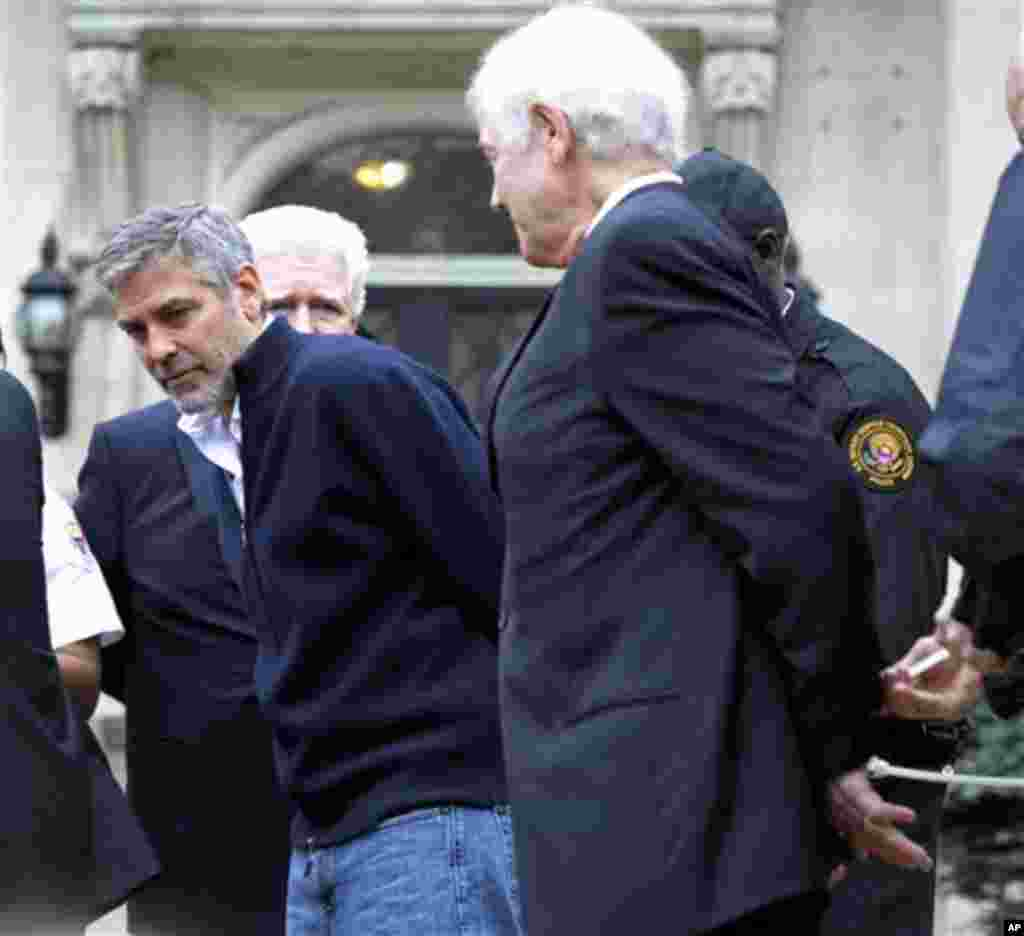 Actor George Clooney, center, Rep. Jim Moran, D-Va, back, and Clooney's father, Nick Clooney, right, are arrested during a protest at the Sudanese Embassy in Washington, Friday, March 16, 2012. The demonstrators are protesting the escalating humanitarian