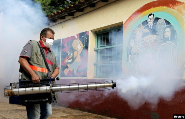A federal health worker takes part in fumigation to prevent the proliferation of mosquitos that transmit the Dengue fever at the San Lorenzo National School, in a low-income neighbourhood of San Lorenzo, Paraguay February 12, 2020. (REUTERS/Jorge Adorno)