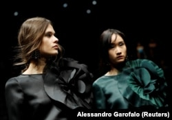 FILE - Models present creations from the Emporio Armani Autumn/Winter 2020 collection during Milan Fashion Week in Milan, Italy, February 21, 2020.