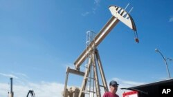 Seorang pengunjung pameran melintas di depan pompa angguk produks minyak dalam pameran di Bismarck, 22 Mei 2014.