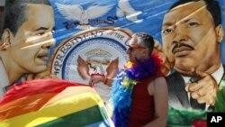 """Un defensor del matrimonio gay ondea una bandera frente al Teatro Paramoun, en Seattle. Obama dijo que sus comentarios sobre los gays fueron obligados por una """"salida"""" del vicepresidente Joe Biden."""