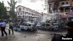 Burnt-out cars are seen at the scene of a blast in Abuja, June 25, 2014. At least 21 people were killed when a suspected bomb tore through a crowded shopping district in the Nigerian capital Abuja during rush hour on Wednesday, police said, adding to the