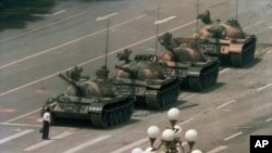 FILE - A Chinese man stands alone to block a line of tanks heading east on Beijing's Cangan Boulevard in Tiananmen Square, in early June 1989.
