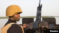 Un officier de la marine patrouille avec une mitrailleuse sur un bateau au large de la côte atlantique dans l'Etat de Bayelsa du Nigeria, 19 décembre 2013.