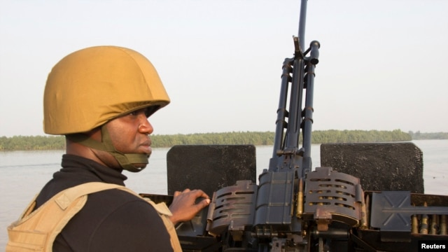 (File) A naval officer mans a machine gun boat off Nigeria's coast. Forty vessels have been attacked by armed gangs in the Gulf of Guinea this year, according to senior US military officials.