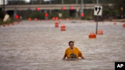 A woman who identified herself as Valerie walks along flooded President Street after leaving her homeless camp after Hurricane Matthew caused flooding, Oct. 8, 2016, in Savannah, Ga.