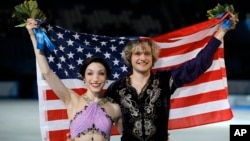 Meryl Davis and Charlie White of the U.S. pose for photographers after placing first in the Olympic ice dance free dance figure skating finals in Sochi, Feb. 17, 2014.