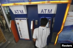 FILE - A man uses an automated teller machine (ATM) machine at a shopping center in Yangon, Burma, May 27, 2012.