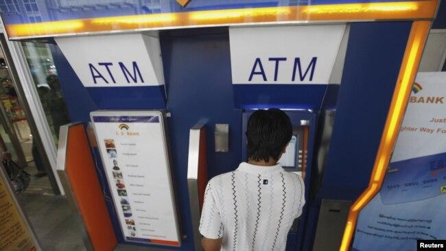 Seorang pria menggunakan ATM untuk mengambil uang di Yangon, Myanmar (foto: dok).