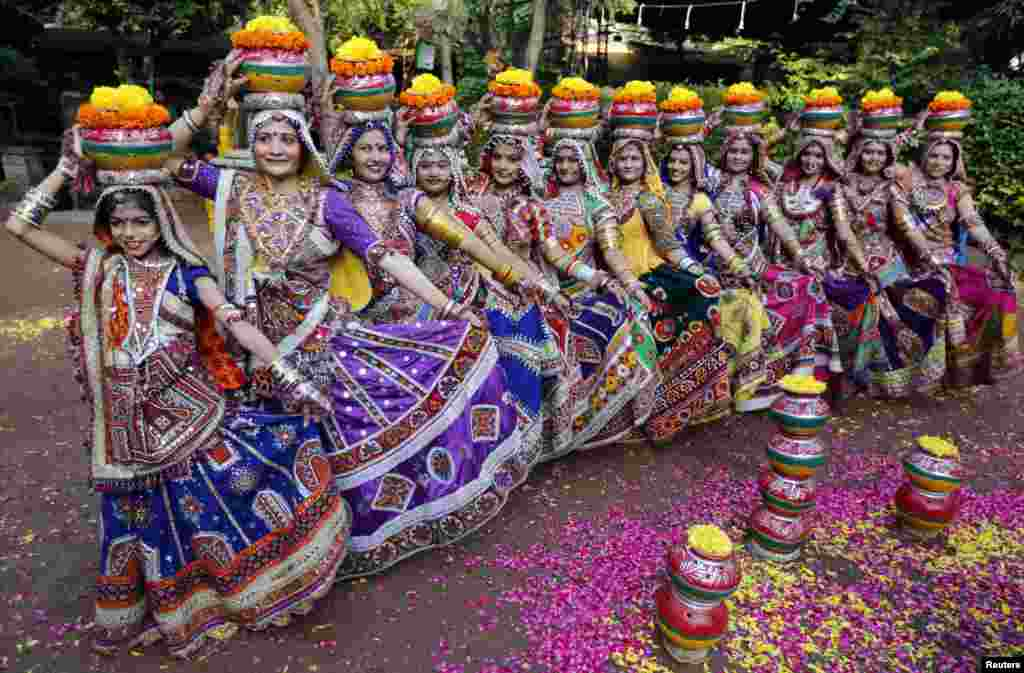 "Women dressed in traditional attire pose as they take part in rehearsals for the ""garba"" dance ahead of Navratri festival in the western Indian city of Ahmedabad."