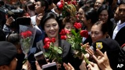 FILE PHOTO - Thailand's former Prime Minister Yingluck Shinawatra, center, receives flowers from her supporters at the Supreme Court after making her final statements in a trial on a charge of criminal negligence in Bangkok, Thailand, Tuesday, Aug. 1, 2017.