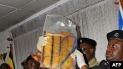 Cảnh sát Uganda cầm một thiết bị nổ tìm thấy sau vụ đánh bom ở Kampala, ngày 13/7/2010