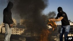 Masked Palestinian youths burn tires during clashes with Israeli police officers, not seen, in the east Jerusalem neighborhood of Issawiyeh, 30 Nov 2010