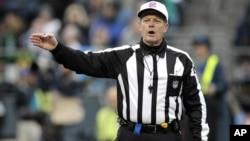 El árbitro Scott Green anuncia una decisión durante un juego de fútbol americano. Luego de criticadas actuaciones de los árbitros sustitutos, la NFL y sus árbitros llegaron un acuerdo que pone fin al paro que había durado tres semanas.
